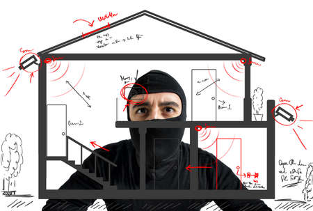 Thief apartment studying security system of a new house Foto de archivo