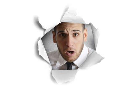 stupor: Concepto de la curiosidad con el hombre mirando a trav�s de un agujero de papel Foto de archivo