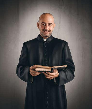 Portret van een gelukkige priester die een bijbel leest Stockfoto