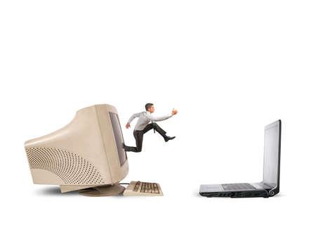 Der Geschäftsmann springend vom alten Computer auf neuen Laptop Standard-Bild