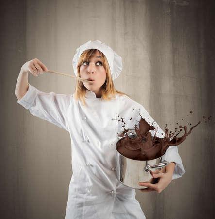 Young girl chef with chocolate in a pot photo