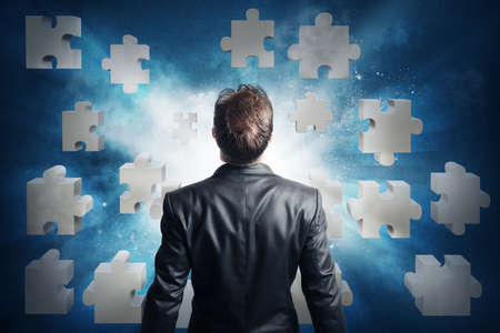 success strategy: Businessman looking for the solution of the puzzle Stock Photo
