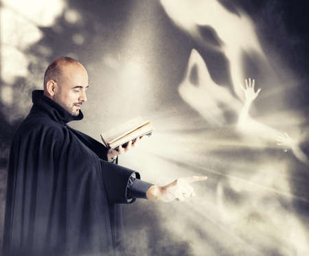 Exorcist priest fights a demon in a dark room Stock Photo