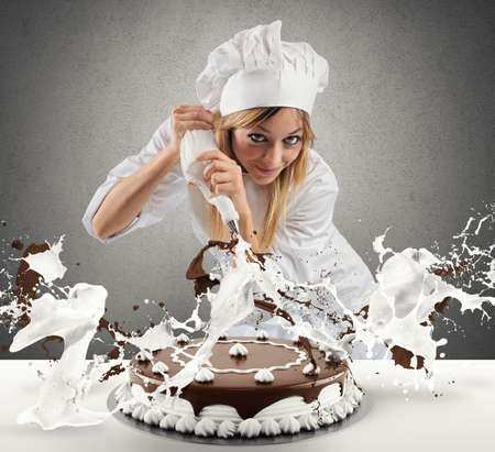 Pastry cook prepares a cake with cream and chocolate