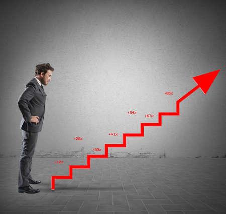 Hombre de negocios con estadísticas positivas de la empresa como una escalera Foto de archivo - 32597334