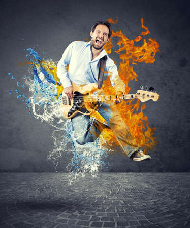 Boy with bass guitar jumps with fire and water photo