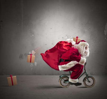Snelle Kerstman op een kleine fiets Stockfoto