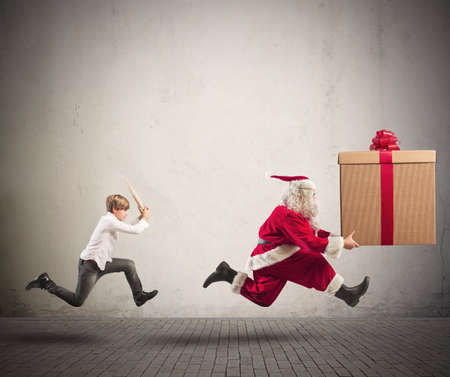 Running angry child chasing Santa Claus with a big present photo