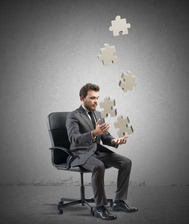 business strategy: Concept of business game with juggler businessman with puzzle Stock Photo