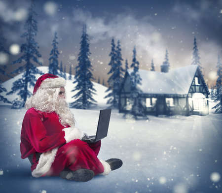 christmas costume: Santa Claus surfs on internet with a laptop