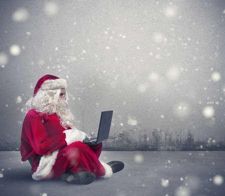 Kerstman surft op internet met een laptop