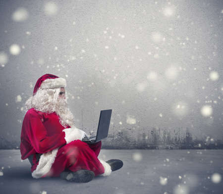 Santa Claus surfs on internet with a laptop photo