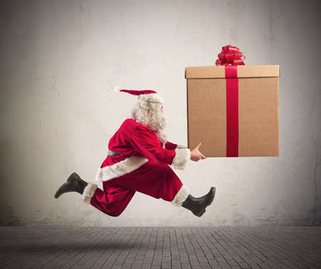 running late: Fast runner Santa Claus with a big present Stock Photo