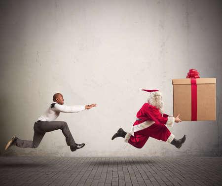 natal: Correndo homem irritado perseguindo Papai Noel com um grande presente Banco de Imagens