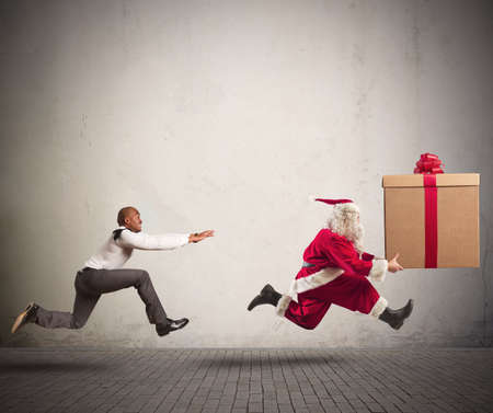 christmas fun: Running angry man chasing Santa Claus with a big present