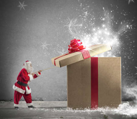 Santa Claus opening a big red gift Stockfoto