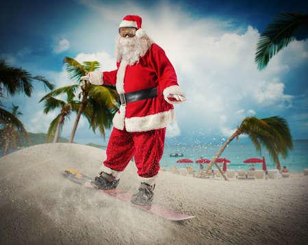 sommer: Lustige Weihnachtsmann geht schnell auf dem Snowboard in einem tropischen Strand