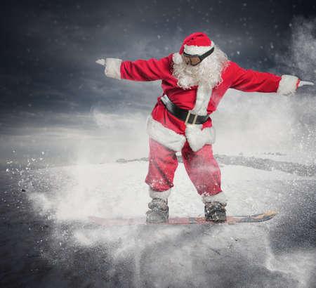 De grappige Kerstman gaat snel op een snowboard Stockfoto