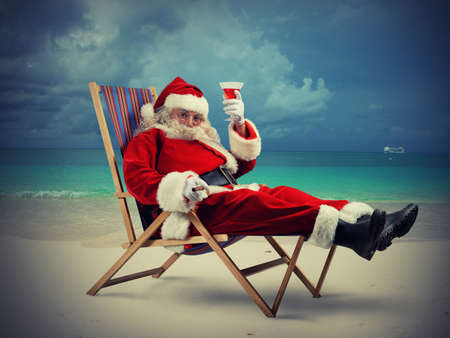 Funny Santa Claus relaxes on the beach