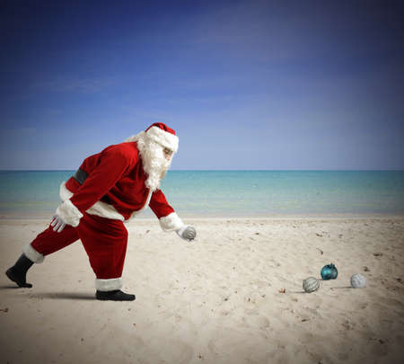 traditional christmas: Santa Claus Playing bowls on the beach Stock Photo