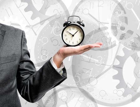 目覚まし時計を保持している実業家と時間の概念 写真素材