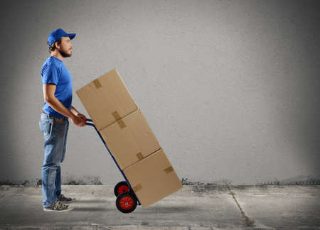 A man carries boxes in a cart photo
