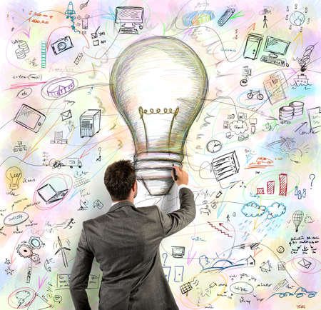 Businessmen draws light bulb in a wall photo