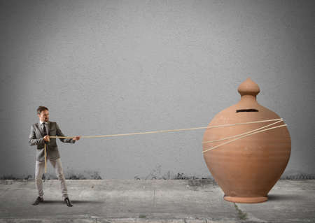 savings risk: Businessman pulls a moneybox with a rope