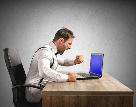 ストレスと怒っているビジネスマンのラップトップで働く