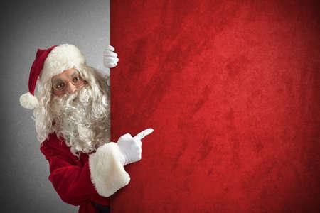 Amazed santa claus indicates a red billboard