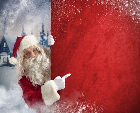 Santaclaus indicates billboard in a Christmas landscape Banco de Imagens - 34043245