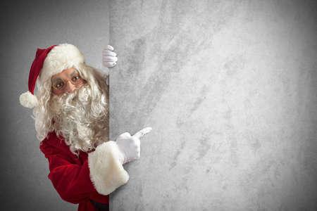 Amazed santa claus indicates a blank billboard Banco de Imagens - 34043247