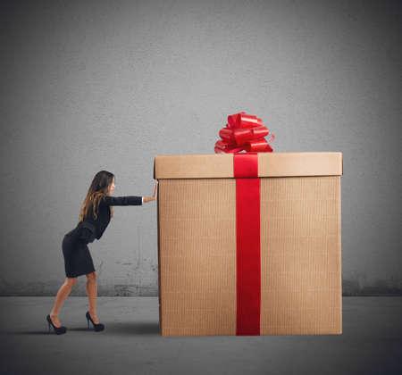 A businesswoman pushing a big Christmas gift