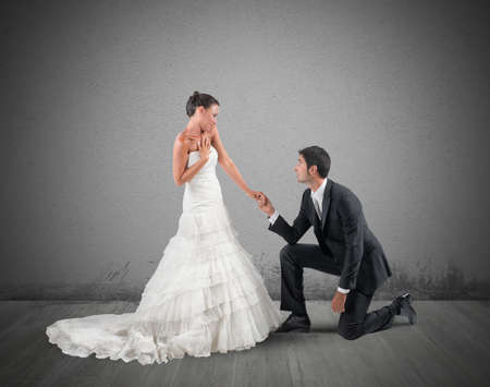 Husband kneels for a romantic marriage proposal photo