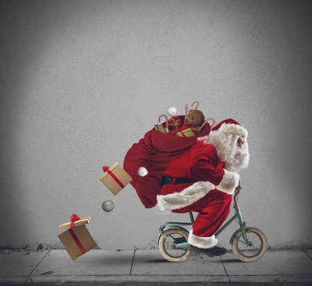 Papá Noel que entrega los regalos con una pequeña bicicleta Foto de archivo - 34279955