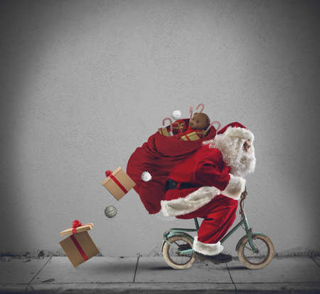 Santaclaus delivering gifts with a small bicycle