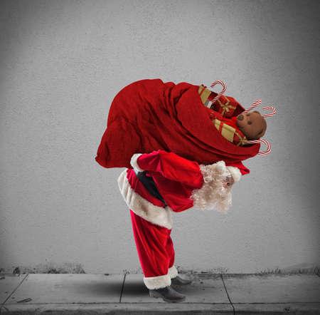 santa clos: Pap� Noel con un saco rojo de regalo pesada Foto de archivo