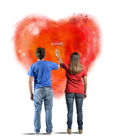 Couple drawing a heart in a wall photo