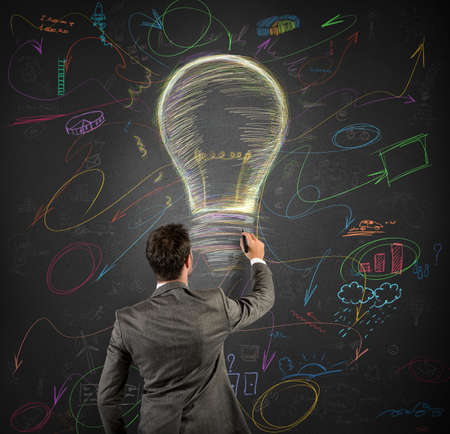 Businessmen draws a light bulb in a blackboard