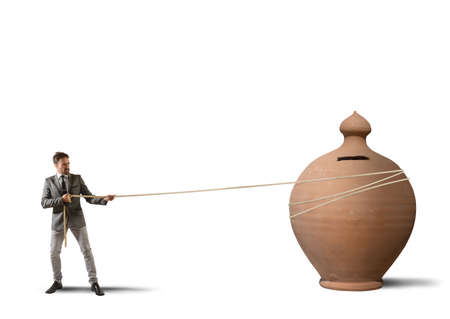 pulling money: Businessman pulls a moneybox with a rope
