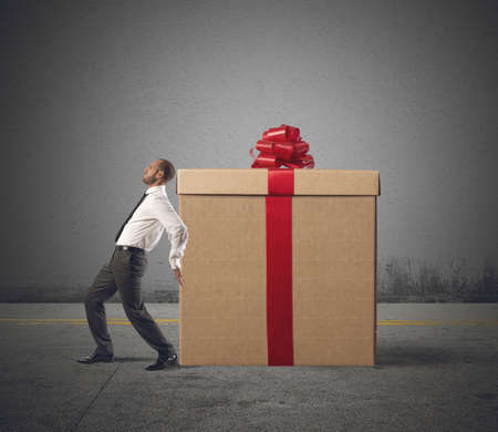 tired businessman: A tired businessman pushes heavy great gift
