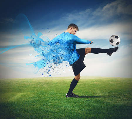 Soccer player kicks ball in a field