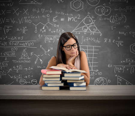 graph theory: A young teacher concentrated reading a book Stock Photo