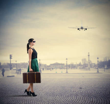 mujer con maleta: Viajero de la mujer con clase camina en una plaza Foto de archivo