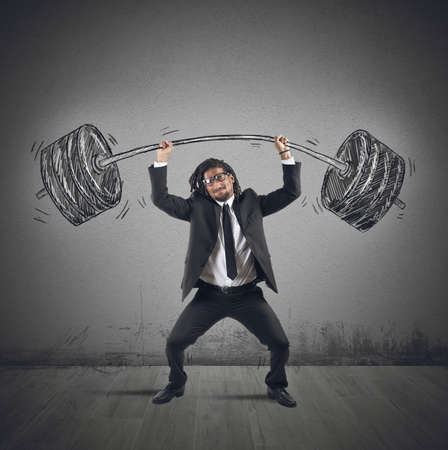 strives: Businessman strives to keep a heavy balancer
