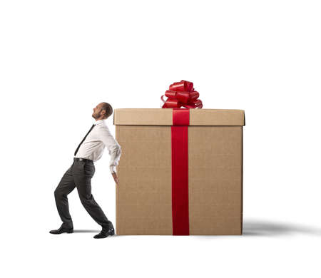 pushes: A tired businessman pushes heavy great gift