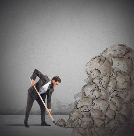 arduous: Businessman digs to remove an obstacle rock