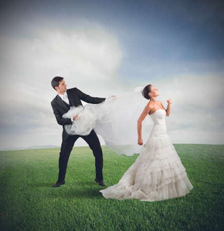 angry couple: Husband pulls the bride who runs away Stock Photo