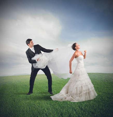 angry person: Marido tira de la novia que huye Foto de archivo