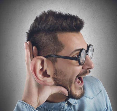 stupor: Nerd hombre escucha con curiosidad chismosa Foto de archivo
